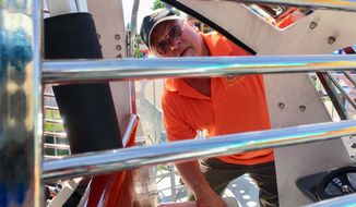 """In this Thursday, Aug. 9, 2018, photo, Illinois Department of Labor amusement ride safety inspector Brian Brown inspects """"Charlie Chopper,"""" a ride in the midway of the Illinois State Fair in Springfield, Ill. Six Labor Department inspectors spent four days last week going over approximately 65 carnival rides running at the state fair through Sunday. (AP Photo/John O'Connor)"""
