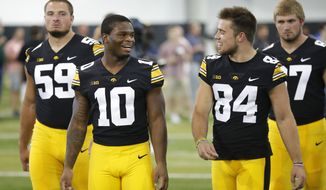 Iowa running back Mekhi Sargent (10) talks with wide receiver Nick Easley (84) during an NCAA college football media day, Friday, Aug. 10, 2018, in Iowa City, Iowa. (AP Photo/Charlie Neibergall)