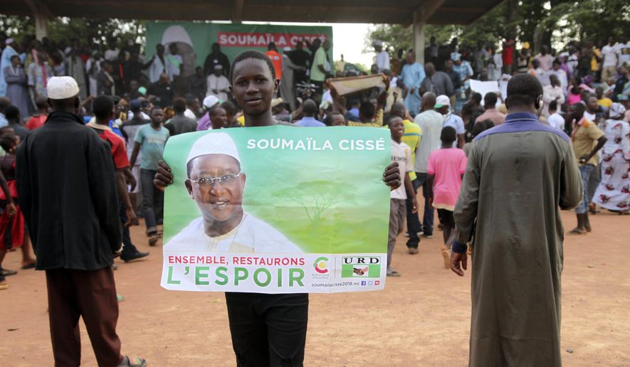 FILE- In this Monday July 16, 2018, file photo a supporter of Soumaila Cisse, Opposition Presidential candidate with Union for the Republic and Democracy party hold a poster that reads '' Together lets restore hope'', during an election campaign rally in Yanfolila, Mali. Mali's first round of voting last month saw electoral agents killed and voting materials destroyed by extremists linked to al-Qaida, and now in a run-off round two election Sunday Aug. 12, 2018, incumbent President Ibrahim Boubacar Keita faces off against Soumaila Cisse. (AP Photo/Baba Ahmed, File)