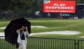 A patron takes a photo as play was suspended for the rest of the day during the second round of the PGA Championship golf tournament at Bellerive Country Club, Friday, Aug. 10, 2018, in St. Louis. Play was suspended due to heavy rain. (AP Photo/Charlie Riedel)