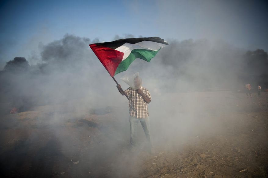 A Palestinian protester wore a plastic bag as protection from teargas during a protest Friday at the Gaza Strip's border with Israel. (Associated Press/File)