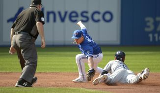 Tampa Bay Rays' Kevin Kiermaier, right, slides safely into second base ahead of the tag by Toronto Blue Jays shortstop Aledmys Diaz, center, after hitting a double during the second inning of a baseball game in Toronto, Saturday, Aug. 11, 2018. (Jon Blacker/The Canadian Press via AP)