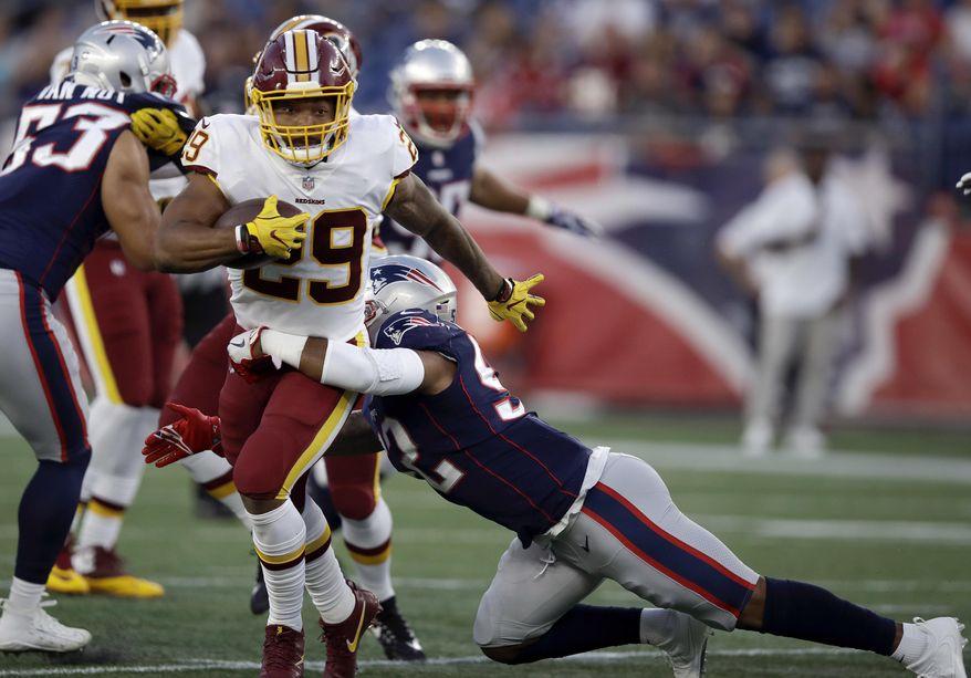 New England Patriots linebacker Elandon Roberts (52) tackles Washington Redskins running back Derrius Guice (29) during the first half of a preseason NFL football game, Thursday, Aug. 9, 2018, in Foxborough, Mass. (AP Photo/Charles Krupa)