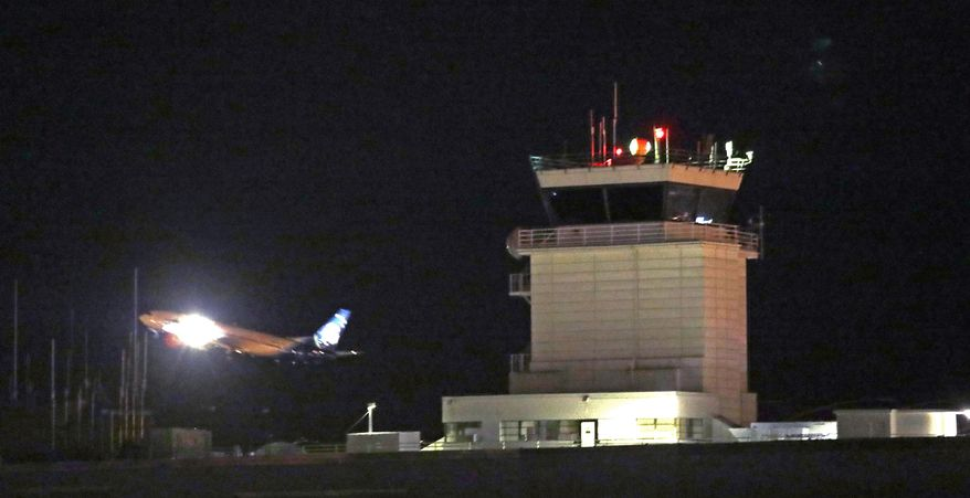 A plane flies past a control tower at Sea-Tac International Airport Friday evening, Aug. 10, 2018, in SeaTac, Wash. An airline mechanic stole an Alaska Airlines plane without any passengers and took off from Sea-Tac International Airport in Washington state on Friday night before crashing near Ketron Island, officials said. (AP Photo/Elaine Thompson)