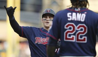 Minnesota Twins designated hitter Tyler Austin, left, approaches home plate after hitting a two-run home run that also scored Miguel Sano (22) during the fifth inning of a baseball game against the Detroit Tigers, Saturday, Aug. 11, 2018, in Detroit. (AP Photo/Carlos Osorio)