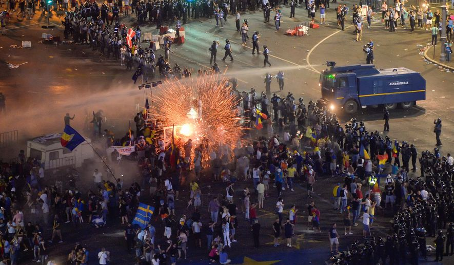 A tear-gas canister explodes as riot police try to clear Victoria Square during Friday's protests outside the government headquarters in Bucharest, Romania. Romanian authorities say hundreds of people including two dozen riot police were injured. (ASSOCIATED PRESS)