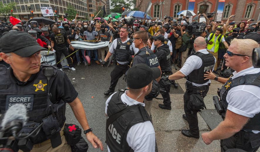 """D.C. Metropolitan Police and Secret Service officers were forced back by counterprotesters outside of a security barrier on 17th street while attempting to escort attendees of the """"Unite the Right 2"""" rally from Lafayette Park in Northwest. (Associated Press)"""