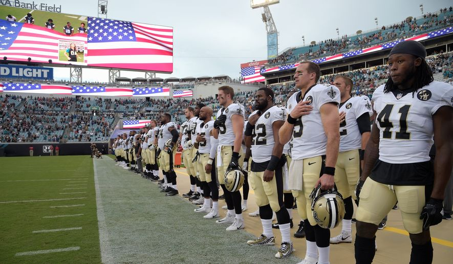 Quarterback Drew Brees (9) leads the New Orleans Saints in standing for the singing of the national anthem before Thursday's preseason game against the Jacksonville Jaguars. President Trump went on the attack after several players across the NFL knelt or raised fists during the anthem. (ASSOCIATED PRESS)