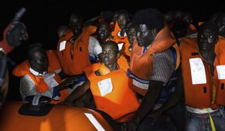FILE -- In this photo taken in the early hours of Thursday night, Aug. 2, 2018 migrants wait to be rescued off the coast of Libya, as rescuers throw life jackets at them and urge them to stay calm. Rescuers from the Spanish non -profit Open Arms saved 87 migrants off the coast of Libya in a dramatic nighttime operation.  The group included eight minors. (AP Photo/Valerio Nicolosi)