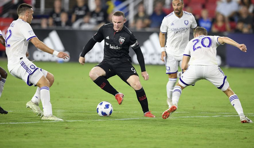 D.C. United forward Wayne Rooney (9) dribbles the ball against Orlando City midfielder Oriol Rosell (20) and defender Shane O'Neill, left, during the first half of an MLS soccer match, Sunday, Aug. 12, 2018, in Washington. (AP Photo/Nick Wass) **File**
