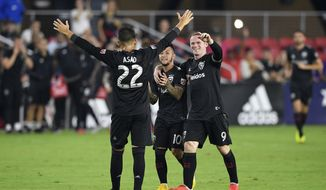 D.C. United midfielder Luciano Acosta (10) celebrates his goal with forward Wayne Rooney (9) and Yamil Asad (22) during the second half of an MLS soccer match against Orlando City, Sunday, Aug. 12, 2018, in Washington. D.C. United won 3-2. (AP Photo/Nick Wass) ** FILE **