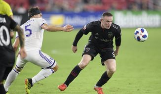 D.C. United forward Wayne Rooney, right, chases the ball against Orlando City midfielder Dillon Powers (5) during the second half of an MLS soccer match, Sunday, Aug. 12, 2018, in Washington. D.C. United won 3-2. (AP Photo/Nick Wass) ** FILE **