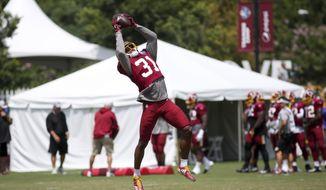 Washington Redskins Fabian Moreau (31) completes a pass at NFL football training camp in Richmond, Va., Sunday, Aug. 12, 2018. (AP Photo/Parker Michels-Boyce)