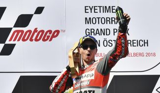 Spain's rider Jorge Lorenzo of the Ducati Team celebrates on the podium after winning the MotoGP race at the Austrian motorcycle Grand Prix at the Red Bull Ring in Spielberg, Austria, Sunday, Aug. 12, 2018. (AP Photo/Kerstin Joensson)