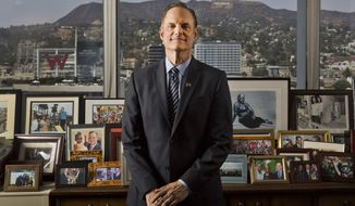 In this Monday, July 30, 2018, photo Michael Weinstein, president of the AIDS Healthcare Foundation poses for a photo of his office overlooking the Hollywood Hills in Los Angeles. The AIDS Healthcare Foundation and Alliance of Californians for Community Empowerment Action are sponsoring a measure known as Proposition 10. The measure would let cities and counties regulate rental fees in buildings current state law shields from such control. (AP Photo/Damian Dovarganes)