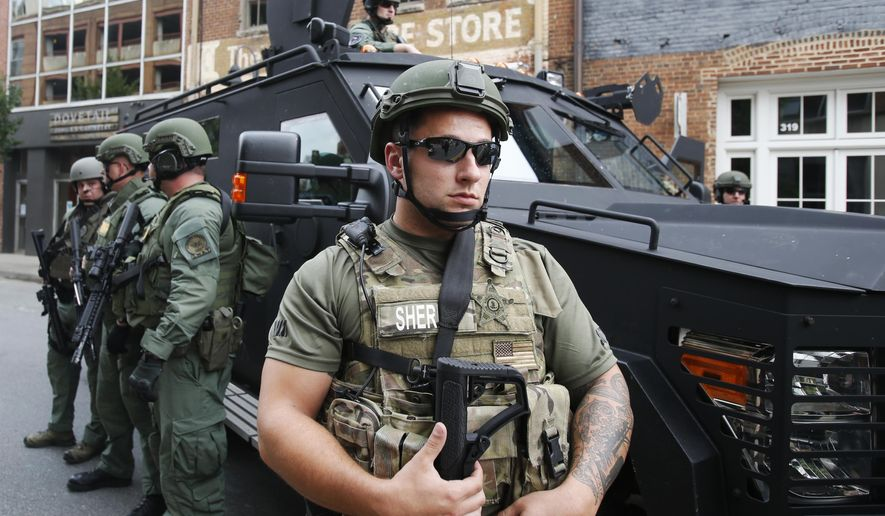 Members of a SWAT team keep an eye on demonstrators marking the one year anniversary of the Unite The Right rally in Charlottesville, Va., Sunday, Aug. 12, 2018. (AP Photo/Steve Helber)