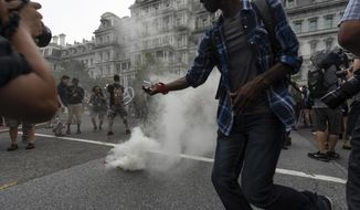 "Journalists photograph a type of smoke grenade placed by Antifa-activists in the middle of 17th street during the ""Unite the Right 2"" rally in Washington, Sunday, Aug. 12, 2018. (Craig Hudson/Charleston Gazette-Mail via AP)"