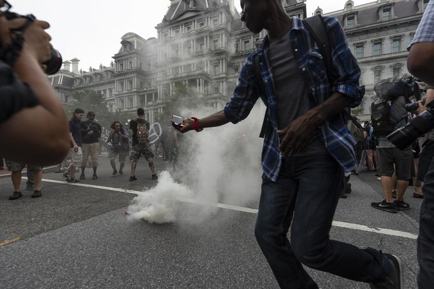 "Journalists photograph a type of smoke grenade placed by antifa-activists in the middle of 17th street during the ""Unite the Right 2"" rally in Washington, Sunday, Aug. 12, 2018. (Craig Hudson/Charleston Gazette-Mail via AP) ** FILE **"