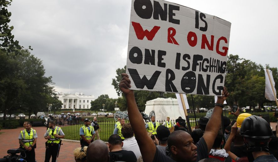 """Demonstrators march near the White House on the one year anniversary of the Charlottesville """"Unite the Right"""" rally, Sunday, Aug. 12, 2018, in Washington. (AP Photo/Jacquelyn Martin)"""