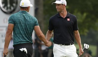 Brooks Koepka, left, is congratulated by playing partner Adam Scott after Koepka won the PGA Championship golf tournament at Bellerive Country Club, Sunday, Aug. 12, 2018, in St. Louis. (AP Photo/Brynn Anderson)