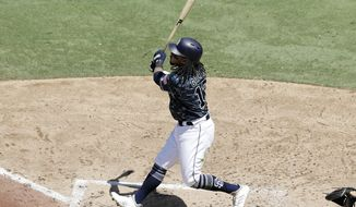 The San Diego Padres' Freddy Galvis watches his grand slam during the third inning of a baseball game against the Philadelphia Phillies, Sunday, Aug. 12, 2018, in San Diego. (AP Photo/Gregory Bull)