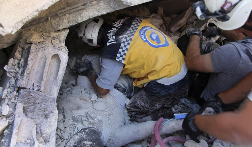 This photo provided by the Syrian Civil Defense White Helmets, which has been authenticated based on its contents and other AP reporting, shows Syrian White Helmet civil defense workers remove a body from the rubble at the scene of an explosion that brought down a five-story building, in the village of Sarmada, near the Turkish border, north Syria, Sunday, Aug. 12, 2018. Syrian opposition activists say the explosion killed several people and wounded many others. The cause of the blast wasn't immediately known. (Syrian Civil Defense White Helmets via AP)