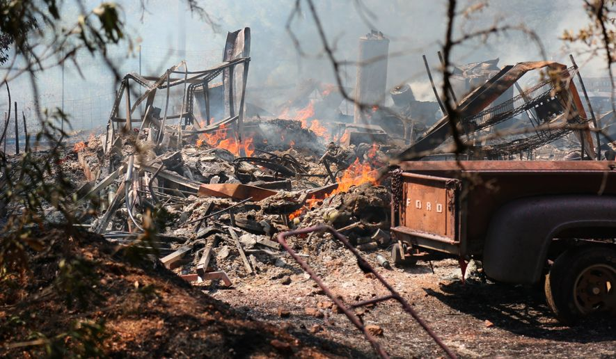 A structure and vehicles burn in the wake of the Oak Fire Sunday, Aug. 12, 2018, near Grass Valley, Calif. (Elias Funez/The Union via AP)