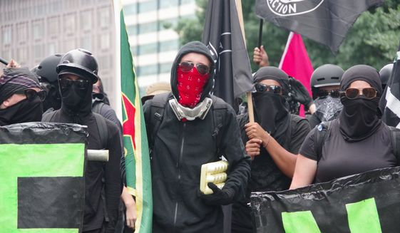"A member of antifa marches in front of the so-called ""black bloc"" that occupied 17th Street and Pennsylvania Avenue in Northwest near the White House. A man holds a carton carrying two-dozen eggs, which were later used to pelt police and journalists, on Aug. 12, 2018. (Washington Times/Julia Airey.)"