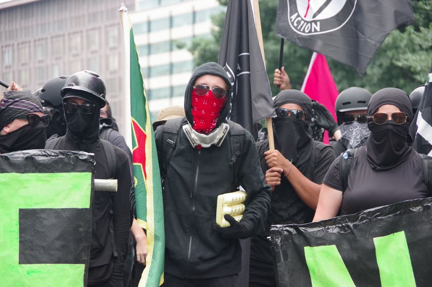 """A member of antifa marches in front of the so-called """"black bloc"""" that occupied 17th Street and Pennsylvania Avenue in Northwest near the White House. A man holds a carton carrying two-dozen eggs, which were later used to pelt police and journalists, on Aug. 12, 2018. (Washington Times/Julia Airey.)"""