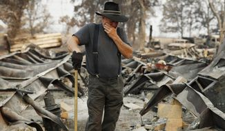 Ed Bledsoe tries to hold back tears as he searches through what remains of his home, Monday, Aug. 13, 2018, in Redding, Calif. Bledsoe's wife, Melody, great-grandson James Roberts and great-granddaughter Emily Roberts were killed at the home in the Carr Fire. (AP Photo/John Locher)