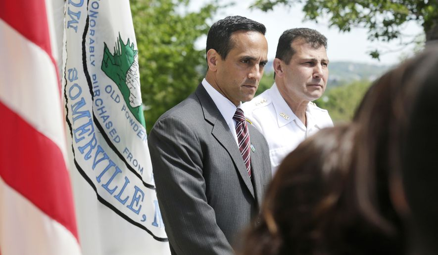 Mayor Joseph Curtatone, left, stands with acting Somerville Police Chief Charles Femino, right, during a news conference regarding immigration in Somerville, Mass., Wednesday, May 21, 2014.  Mayor Curtatone announced that Somerville will be the first community in Massachusetts to bar city police from detaining people simply because of their immigration status. (AP Photo/Charles Krupa)