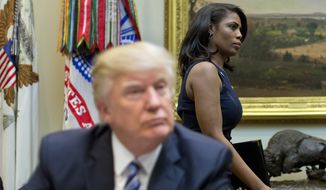 """In this March 12, 2017 file photo, White House Director of communications for the Office of Public Liaison Omarosa Manigault, right, walks past President Donald Trump during a meeting on healthcare in the Roosevelt Room of the White House in Washington. Manigault Newman, who was fired in December, released a new book """"Unhinged,"""" about her time in the White House. (AP Photo/Pablo Martinez Monsivais, File)"""