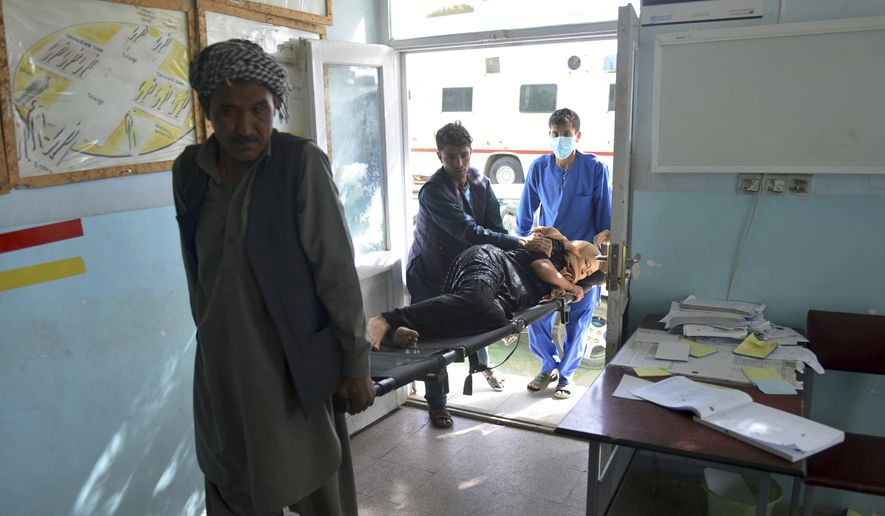 In this Sunday, Aug. 12, 2018, photo, a wounded woman is brought into a hospital in Ghazni province, west of Kabul, Afghanistan. The United States has sent military advisers to aid Afghan forces in Ghazni, where they were struggling on Sunday to regain full control three days after the Taliban launched a massive assault on the eastern city. (AP Photo/Mohammad Anwar Danishyar)