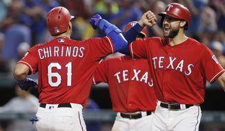 Texas Rangers' Robinson Chirinos (61) is congratulated by Joey Gallo, right, after hitting a three-run home run during the fourth inning of a baseball game against the Arizona Diamondbacks, Monday, Aug. 13, 2018, in Arlington, Texas. (AP Photo/Brandon Wade)