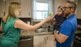 In this Aug. 1, 2018, photo, Lauren Woehr hands her 16-month-old daughter Caroline, held by her husband Dan McDowell, a cup filled with bottled water at their home in Horsham, Pa. In Horsham and surrounding towns in eastern Pennsylvania, and at other sites around the United States, the foams once used routinely in firefighting training at military bases contained per-and polyfluoroalkyl substances, or PFAS. EPA testing between 2013 and 2015 found significant amounts of PFAS in public water supplies in 33 U.S. states. (AP Photo/Matt Rourke)