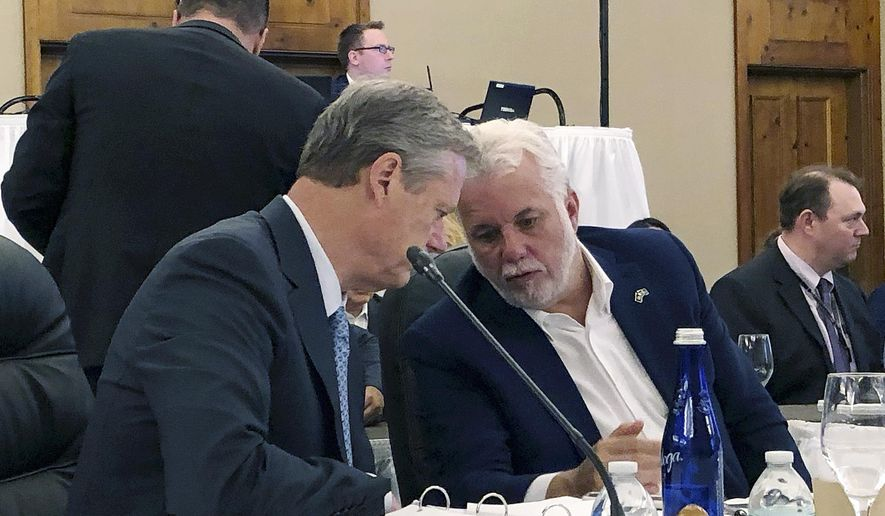 Massachusetts Gov. Charlie Baker, left, and Quebec Premier Philippe Couillard confer during the Conference of New England Governors and Eastern Canadian Premiers on Monday, Aug. 13, 2018, in Stowe, Vt. (AP Photo/Lisa Rathke)