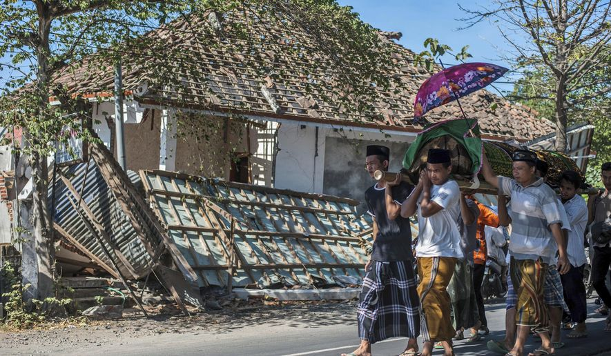 Indonesian men carry the body of a victim of last week's earthquake past a damaged building during a funeral in Gangga, Lombok Island, Indonesia, Sunday, Aug. 12, 2018. Hundreds of people were killed while nearly 400,000 people are left homeless or displaced after the powerful earthquake rocked the popular tourist island on Aug. 5. (AP Photo/Fauzy Chaniago)