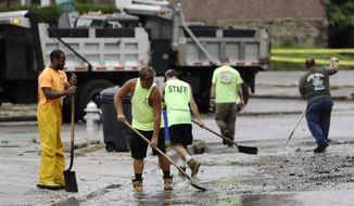 Workers clean up debris swept into the street during flooding in Upper Darby, Pa., Monday, Aug. 13, 2018. Authorities say heavy rains have been causing flooding and prompting road closures and rescues of people from stranded cars in central and southeastern Pennsylvania. (AP Photo/Matt Rourke)