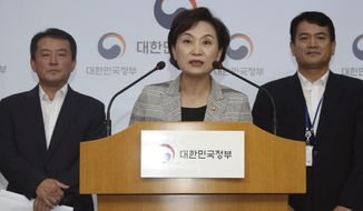 South Korean Minister of Land Infrastructure and Transport, Kim Hyun-mee, center, speaks at a press conference at the government complex in Seoul, South Korea, Tuesday, Aug. 14, 2018. South Korea will ban driving recalled BMWs that haven't received safety checks following dozens of fires the German automaker has blamed on a faulty exhaust gas component. (Kim Seung-doo/Yonhap via AP)