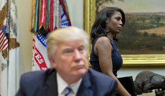 "FILE - In this March 12, 2017 file photo, White House Director of communications for the Office of Public Liaison Omarosa Manigault, right, walks past President Donald Trump during a meeting on healthcare in the Roosevelt Room of the White House in Washington. Manigault Newman, who was fired in December, released a new book ""Unhinged,"" about her time in the White House. (AP Photo/Pablo Martinez Monsivais, File)"