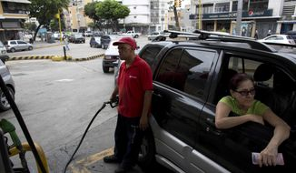FILE - In this March 23, 2017 file photo, an employee pumps gas for a customer at a gas station in Caracas, Venezuela. Venezuelan President Nicolas Maduro said Monday, Aug. 13, 2018 that the cheap gasoline his country's drivers enjoy will soon be sold at world market prices to combat rampant smuggling, but that residents showing a government-issued identification card at the pump will still be able to buy subsidized gasoline. Filling up a tank today costs less than one U.S. cent. (AP Photo/Ariana Cubillos, File)