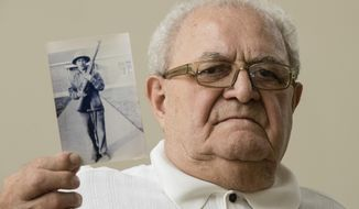 In this July 31, 2018, photo, Dominic Ragucci poses for a portrait in Philadelphia with a photo of his brother, Emil, who was killed in action during World War II. Nearly 70 years after Emil's death in the South Pacific Battle of Tarawa, his remains are scheduled to return home to Philadelphia on Monday, Aug. 13, 2018. (AP Photo/Matt Rourke)