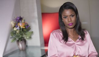 """Former White House staffer Omarosa Manigault Newman speaks during an interview with The Associated Press, Tuesday, Aug. 14, 2018, in New York. Manigault Newman declared she """"will not be silenced"""" by President Donald Trump, remaining defiant as her public feud with her former boss shifted from a war of words to a possible legal battle. (AP Photo/Mary Altaffer)"""