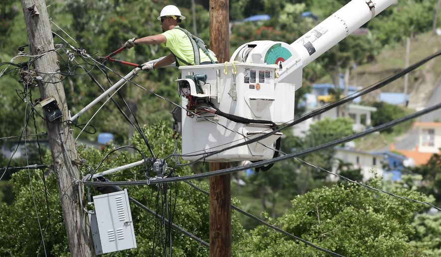 FILE- In this May 16, 2018 file photo, a worker from the Cobra Energy Company, contracted by the Army Corps of Engineers, installs power lines in the Barrio Martorel area of Yabucoa, Puerto Rico. Officials said on Tuesday, Aug. 14, that the power has been restored to the entire island for the first time since Hurricane Maria struck nearly 11 months ago. (AP Photo/Carlos Giusti, File)