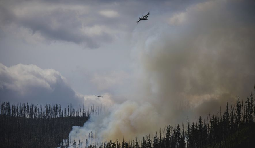 "In this Sunday, Aug. 12, 2018 photo provided by the National Park Service, a Canadian CL-215 ""superscooper"" airplane drops water on the Howe Ridge Fire in Glacier National Park, Mont. A wildfire destroyed structures and forced evacuations Monday from the busiest area of Montana's Glacier National Park, as officials in California prepared to reopen Yosemite National Park Tuesday following a nearly three-week closure at the height of the summer season. (National Park Service via AP)"