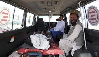 An injured boy rides in an ambulance on the Ghazni highway, in Maidan Shar, west of Kabul, Afghanistan, Monday, Aug. 13, 2018. Afghan forces battled the Taliban in the eastern city of Ghazni a key provincial capital, for the fourth straight day on Monday, following a massive assault on the eastern city last week that overwhelmed its defenses and allowed insurgents to capture several parts of it, officials said. (AP Photo/Rahmat Gul)