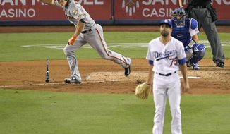 San Francisco Giants' Nick Hundley, left, celebrates as he hits a two-RBI single as Los Angeles Dodgers relief pitcher Scott Alexander, center, watches along with catcher Austin Barnes during the ninth inning of a baseball game, Monday, Aug. 13, 2018, in Los Angeles. (AP Photo/Mark J. Terrill)