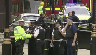 In this frame grab taken Tuesday, Aug. 14, 2018, armed police detain a man, fifth right, who was in a car that crashed into security barriers outside the Houses of Parliament stands to the right of a bus in London. London police say that a car has crashed into barriers outside the Houses of Parliament and that there are a number of injured. (SKY News via AP)