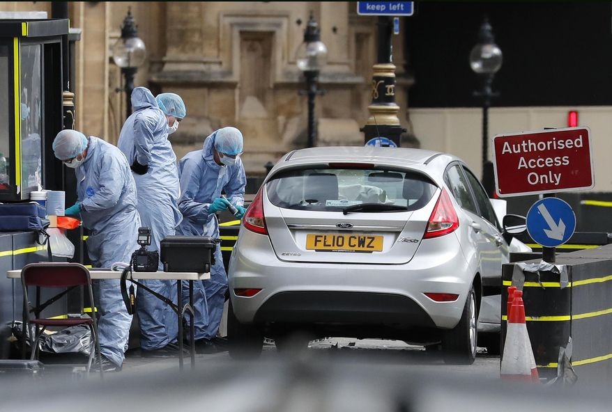 Forensics officers work near the car that crashed into security barriers outside the Houses of Parliament in London, Tuesday, Aug. 14, 2018. Authorities said in a statement Tuesday that a man in his 20s was arrested on suspicion of terrorist offenses after a silver Ford Fiesta collided with a number of cyclists and pedestrians before crashing into the barriers during the morning rush hour. (AP Photo/Frank Augstein)