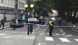Police patrol on Millbank, in central London, after a car crashed into security barriers outside the Houses of Parliament, in London,  Tuesday, Aug. 14, 2018. London police say that a car has crashed into barriers outside the Houses of Parliament and that there are a number of injured. (Sam Lister/PA via AP)